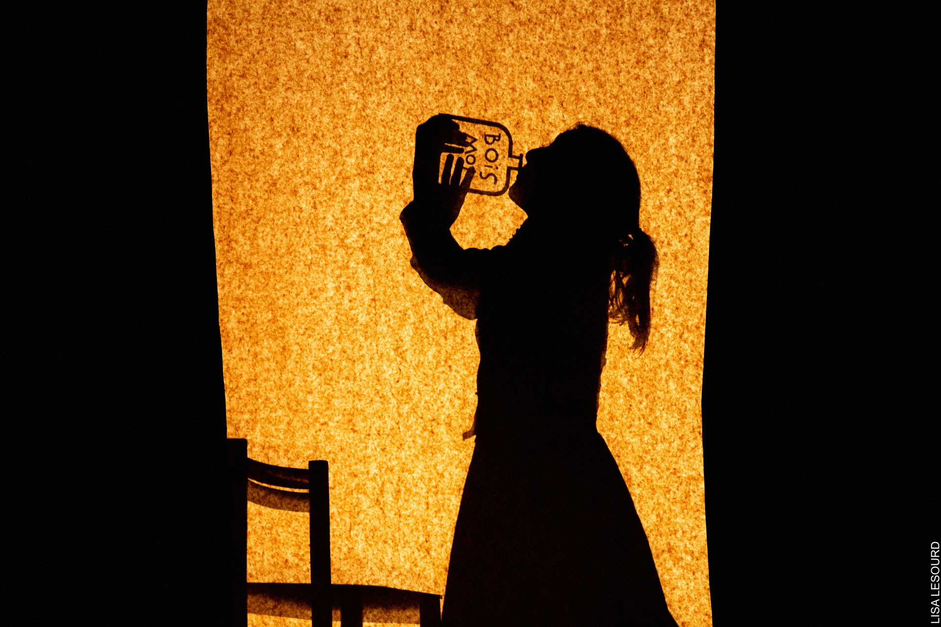 La silhouette d'Alice se dessine en ombres chinoises. Elle boit à une bouteille portant l'inscription bois-moi